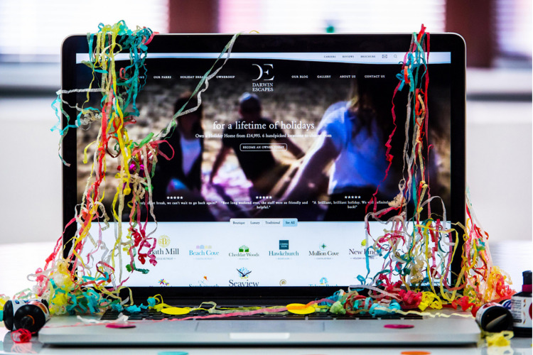 New website being shown on a laptop covered in confetti