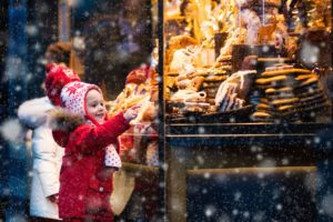 Young child choosing food off a stall at a Christmas market