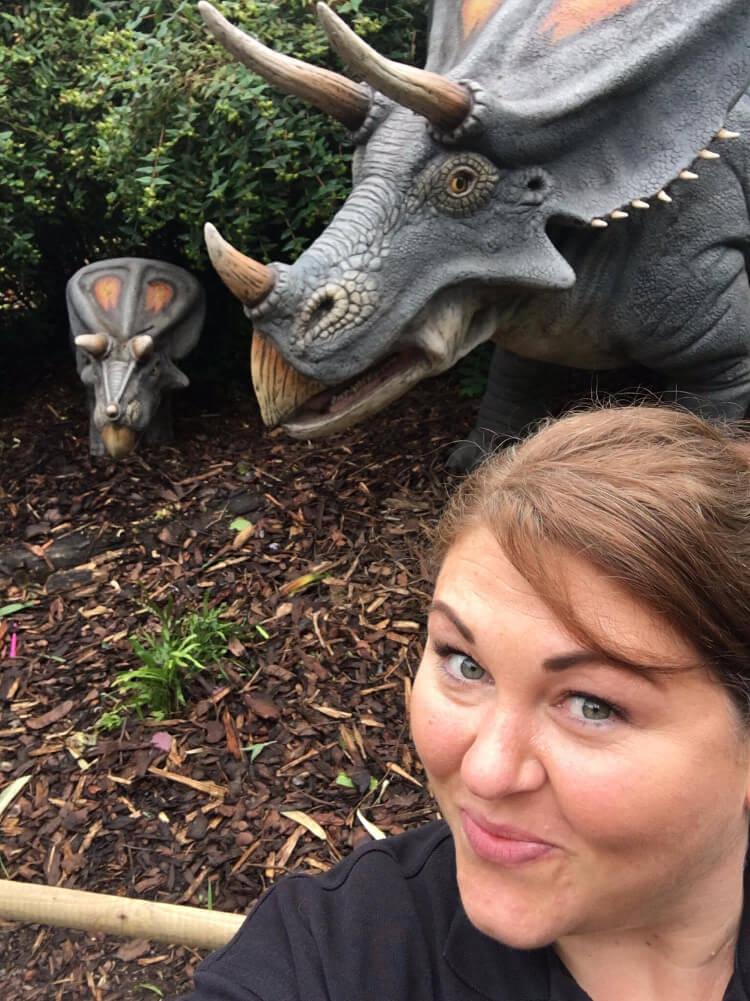 Darwin Escapes team member posing by a model dinosaur