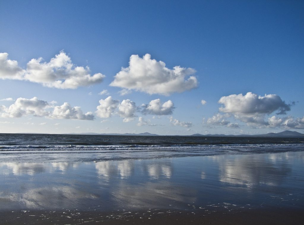 Photo of harlech beach on a sunny day with clouds in the sky