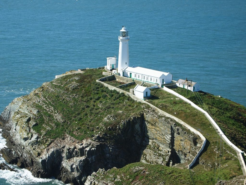 lighthouse on top of the hill looking out to sea