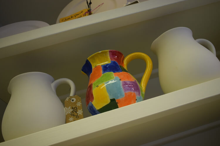 Photo of pottery milk jugs with one painted on display