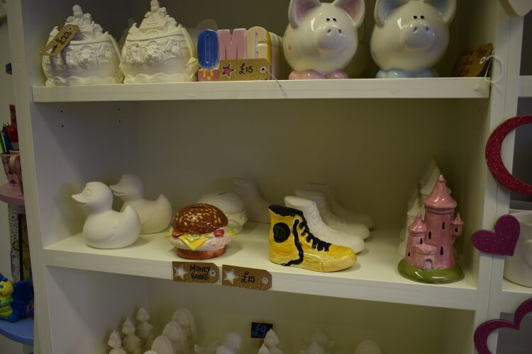 Shelf of pottery with both unpainted and painted pottery