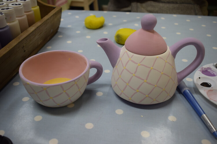 Photo of a pottery teapot and cup that has been painted in light pink tones