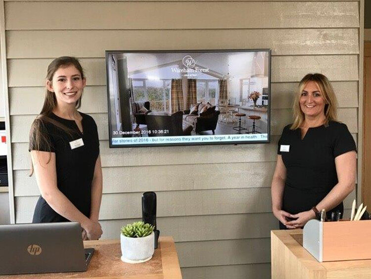 Two of Wareham Forest's receptionists posing for a photo behind reception