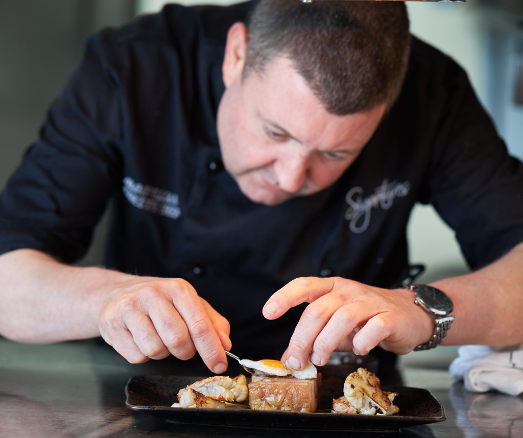Owner of Signatures restaurant plating up food