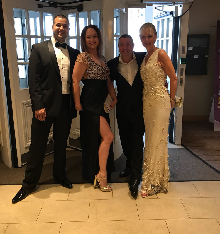Owners of signatures, Jimmy and Louise, pose for a photo with their head chef and his girlfriend. They are all wearing black tie.