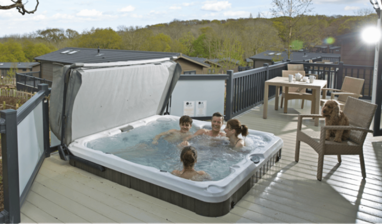 Family sitting in a hot tub with their dog watching