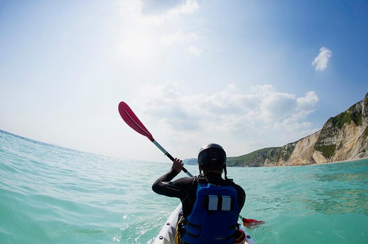 Shot of a man kayaking in the ocean taken from behind