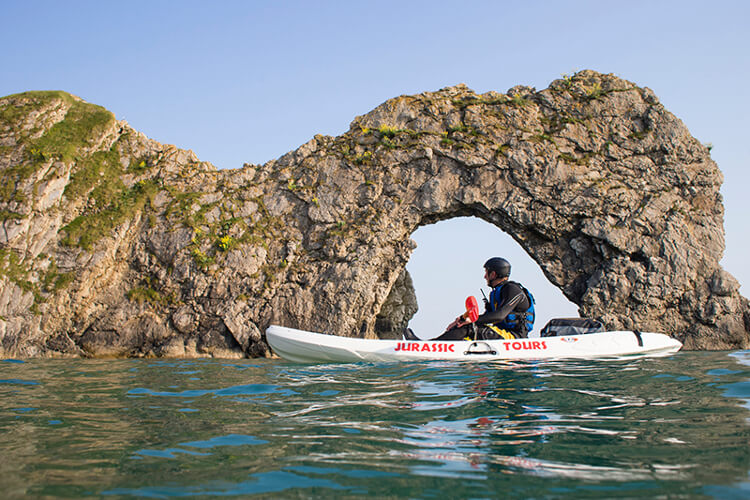 Man kayaking alongside durdle door in Dorset