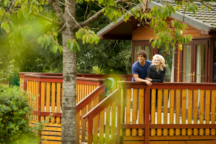 Couple on standing on a decking at on a lodge at Cheddar Woods