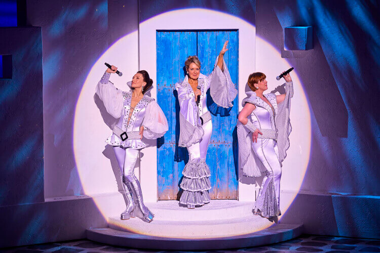 Female cast members posing for a photo during a performance of Mammia Mia