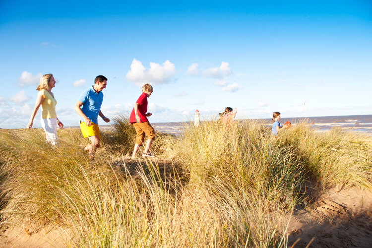 Family running along the sand dunes at Talacre beach
