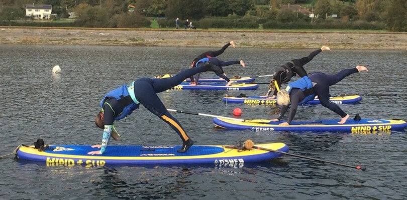 Group of people taking part in paddleboard yoga