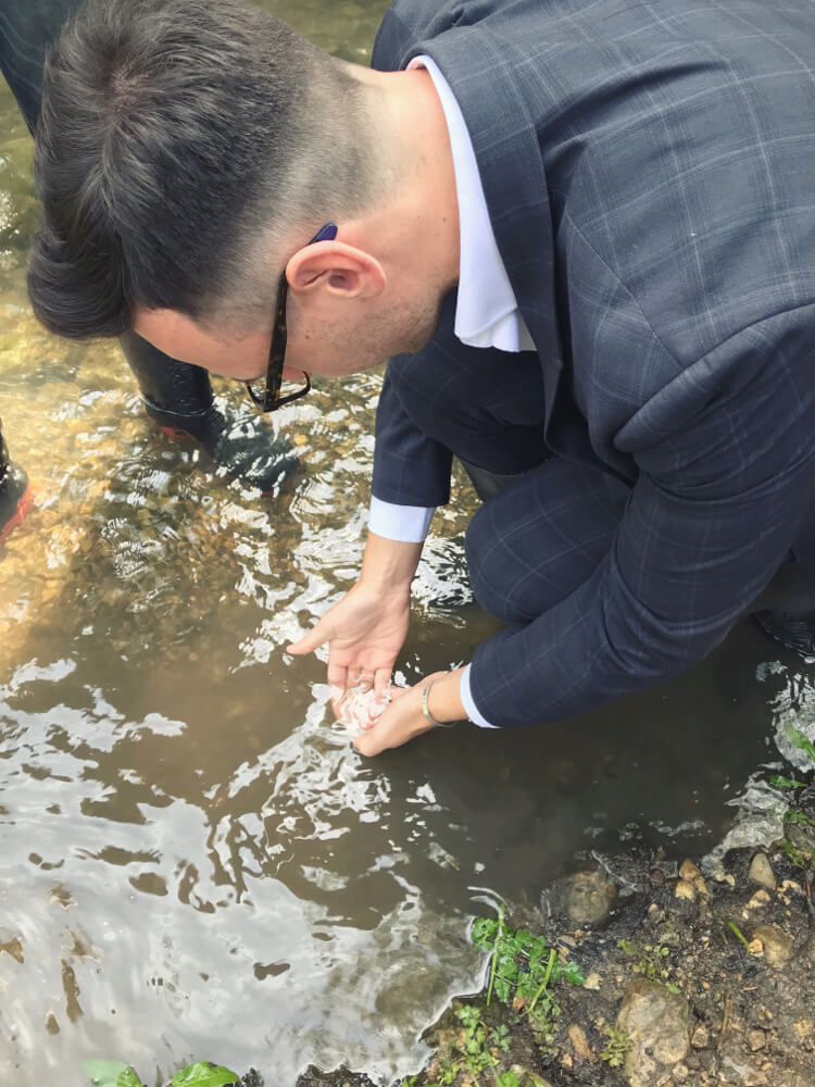 Will, Bath Mill manager, releasing eels into the Newton Brook
