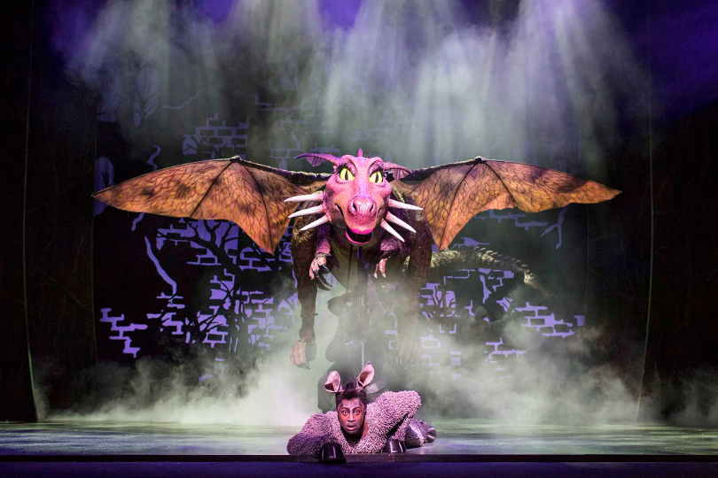Photo of Marcus Ayton as Donkey with the Dragon during a perfomance of Shrek the Musical
