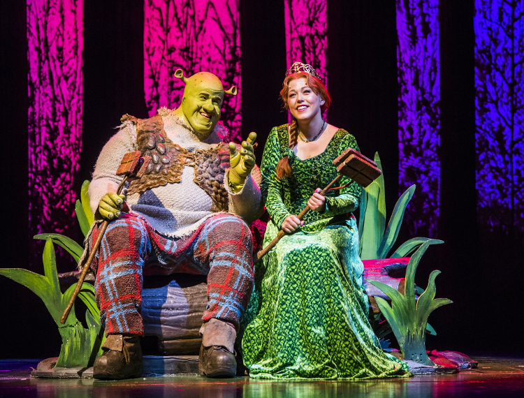 Shrek and Fiona posing for a photo on stage during a performance