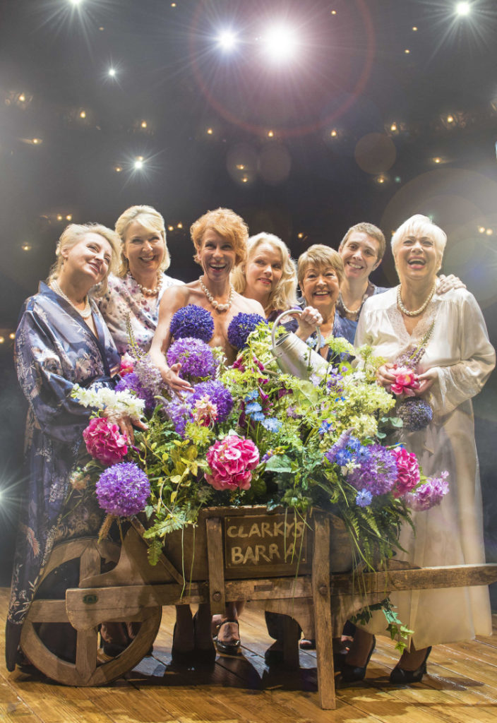 Cast of calendar girls posing for a photo on stage