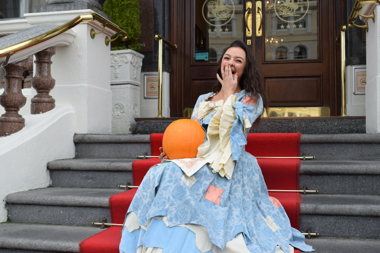 Photo of Cinderella holding a pumpkin posing for a photo