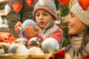 Girl is at the Christmas Market with her mother and is enjoying the Christmas Baubles.