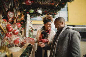 Couple looking at a gift to buy from a stall at the Christmas market