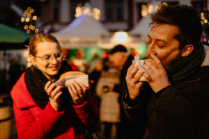 Young couple eating food bought from a christmas market