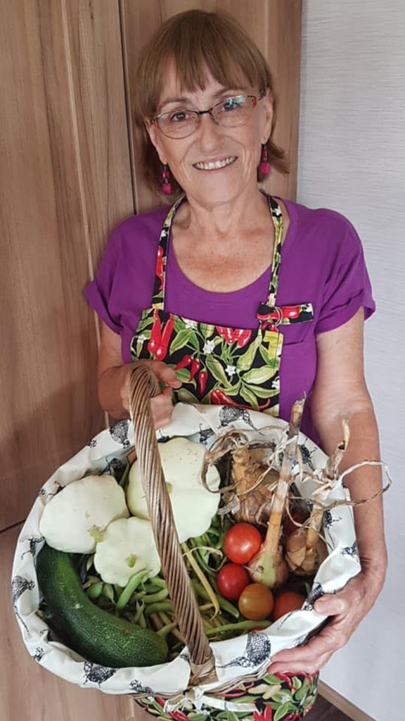 Mickie holding her basket vegetables grown at New Pines' allotment