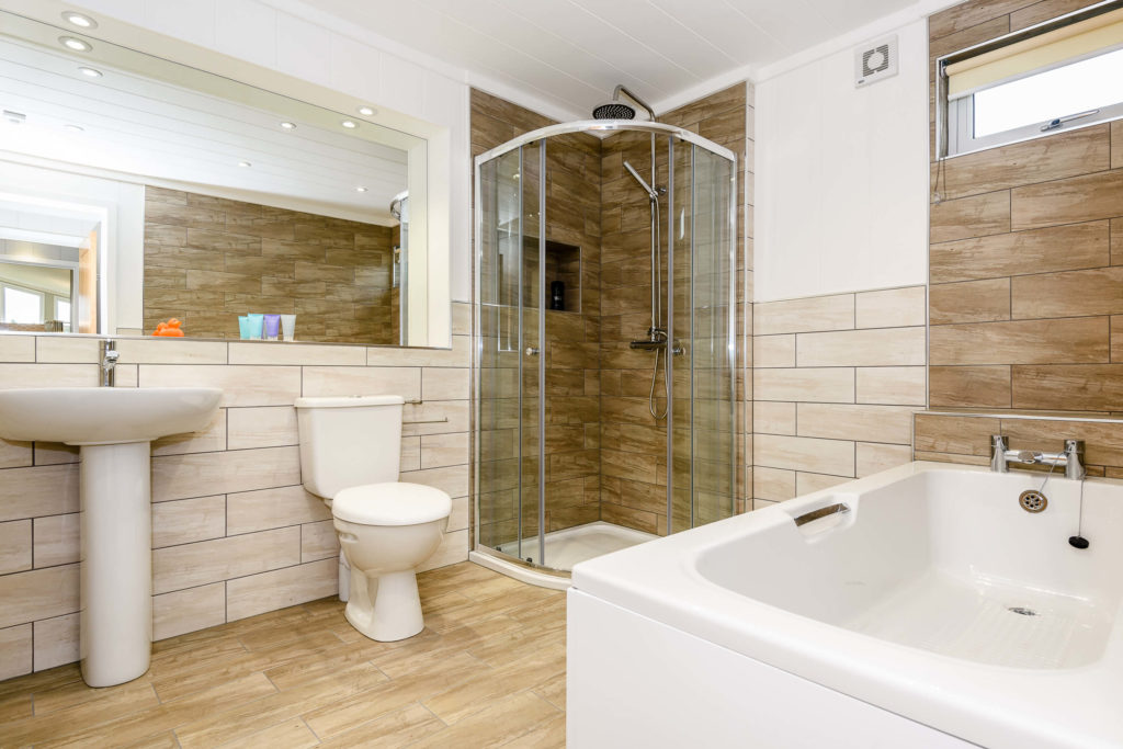 bathroom with standing shower, toilet, sink and separate bath