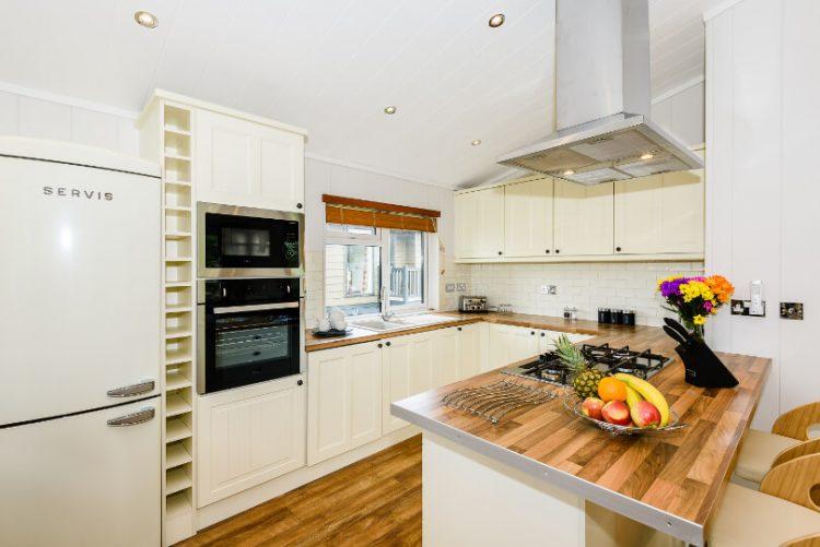 kitchen area with fridge/freezer, kitchen island and kitchen worktops