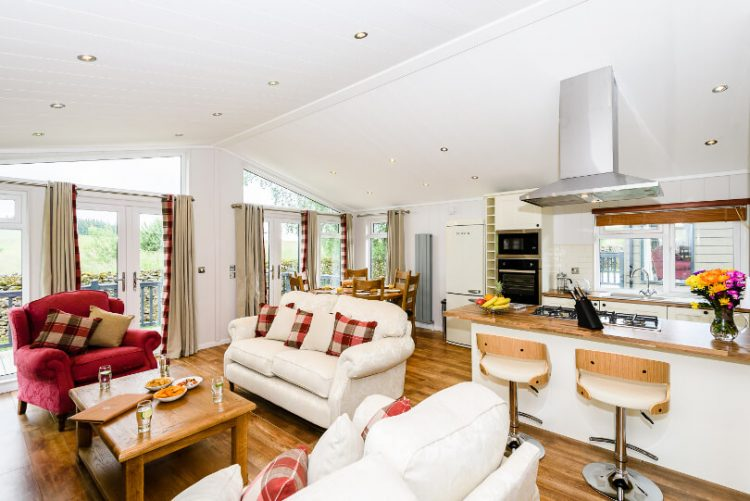 wide view of living room including sofas, armchair, kitchen island and breakfast stools