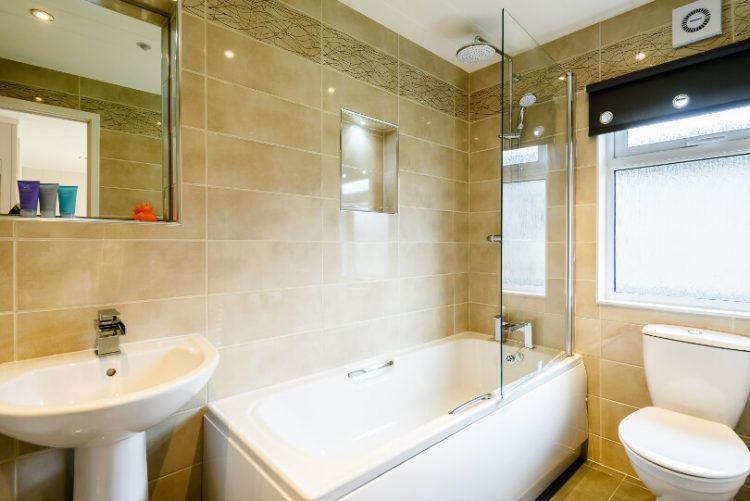 tiled bathroom with integrated shower/bath toilet and basin