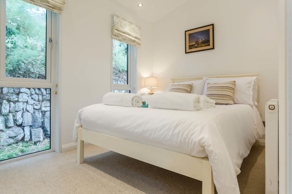 Interior shot of master bedroom in a lodge at Mullion Cove