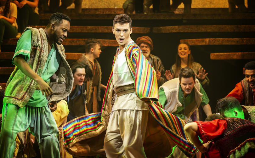 The cast of Joseph posing for a photo on stage