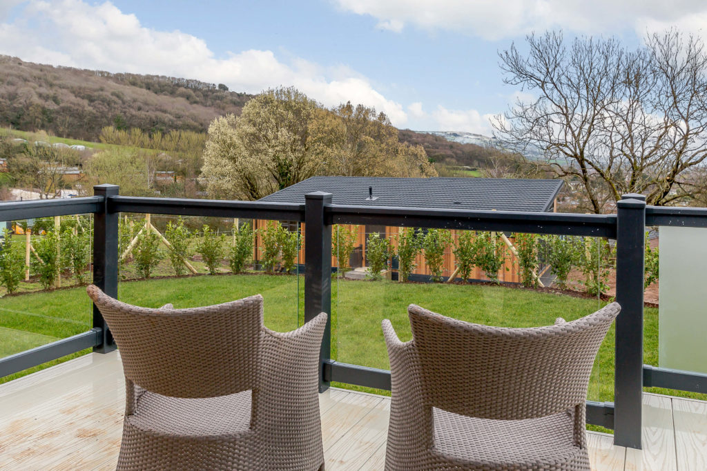 Photo of rattan chairs on a decking on a Cheddar Woods Lodge