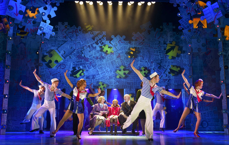 The cast of Annie the Musical dancing on stage during a performance