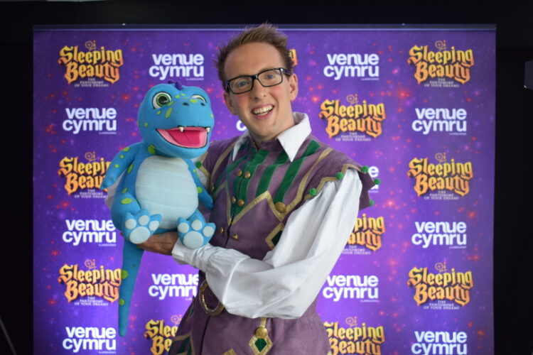 Cast member from sleeping beauty panto posing for a photo with his puppet