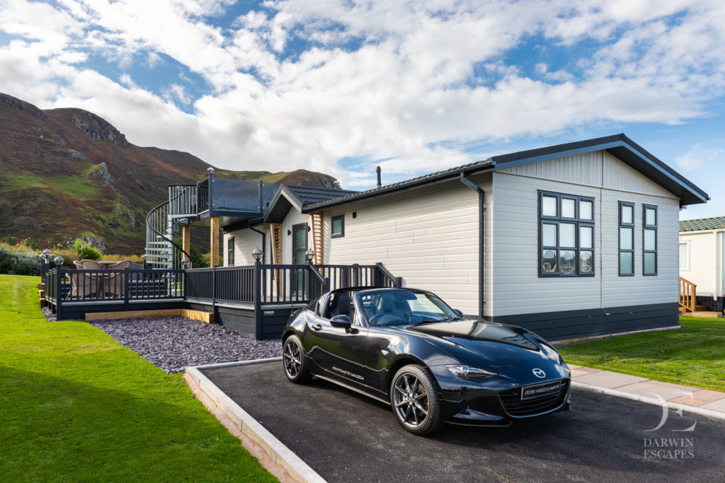 Exterior shot of the Bowmoor lodge and a Mazda MX5