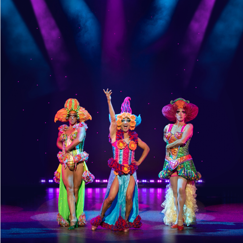 Three cast members of the Priscilla Queen of the Desert posing for a photo