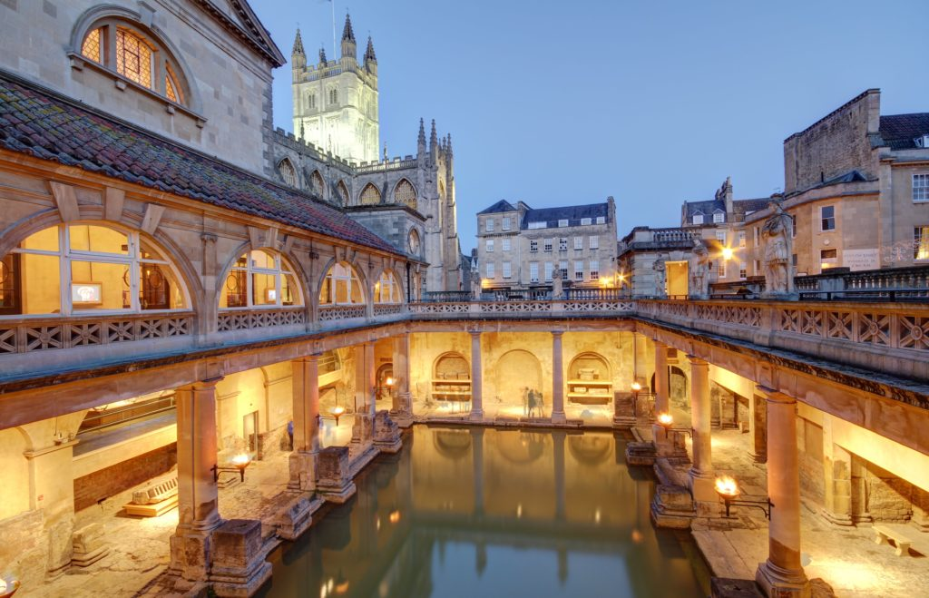 An image of the Roman Baths in Bath as night falls with lights on around the baths
