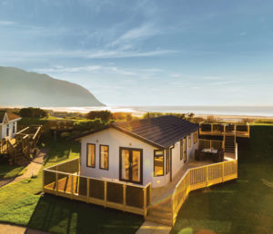 larger ownership lodge at aberconwy resort at sunset, with the beach, sea and mountain in the backdrop