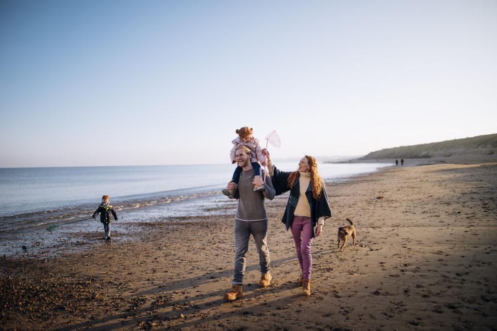 A young family enjoy walking across a beach