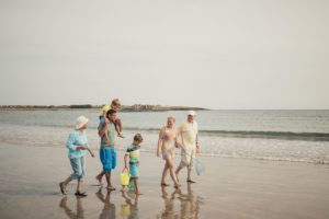 A large family take a walk on the beach together.