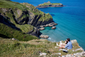 Couple sat together on Mullion Cove looking out to the ocean