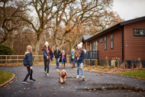 Family walking their dog past a lodge at Norfolk Woods