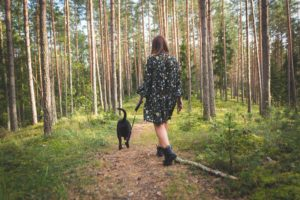 Woman and her dog walking through a forest