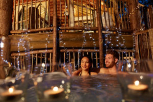 couple in hot tub at night with candles