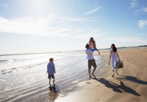 family walking on beach in the sunshine with clear skys and blue water