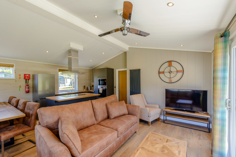 Hulme End living room interior with clock on the wall, tv, sofa, kitchen and dining area