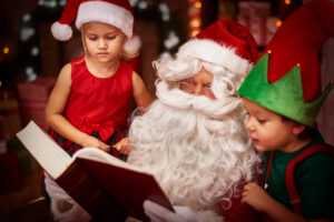 Two children stood with Santa reading through their Christmas list