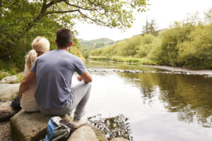 couple sat on rocks near waters edge in the Lake District